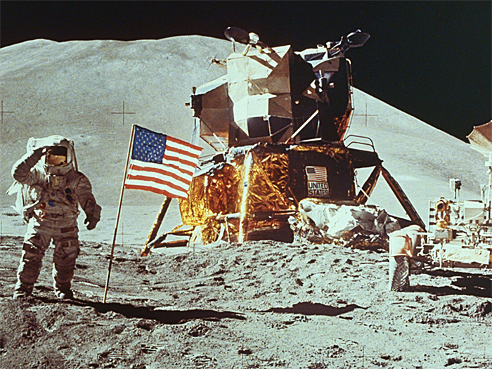 Apollo astronaut on the Moon with Lunar Module and flag