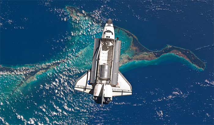 Space Shuttle Atlantis in orbit above ocean reef