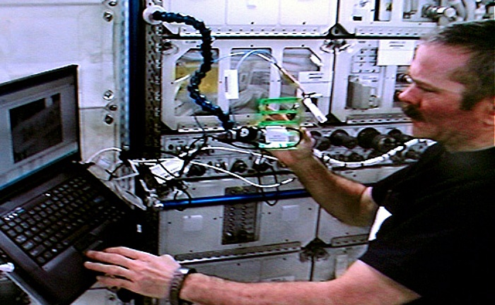 Canadian astronaut Chris Hadfield performing microscopic survey of NanoRacks protein crystal samples aboard International Space Station (ISS)