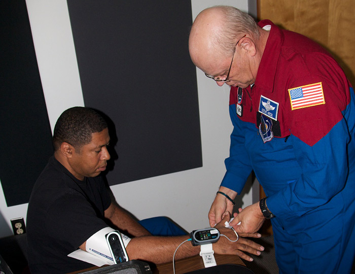 Citizen-astronaut candidate Michael Johnson (left) prepares to evaluate biomedical sensors with help from Lt. Col. Steve Heck
